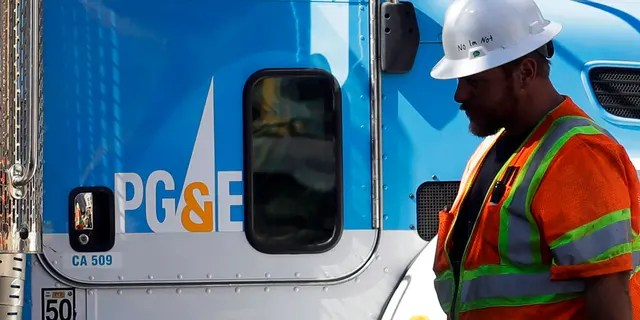 In this Aug. 15, 2019, file photo, a Pacific Gas & Electric worker walks in front of a truck in San Francisco.