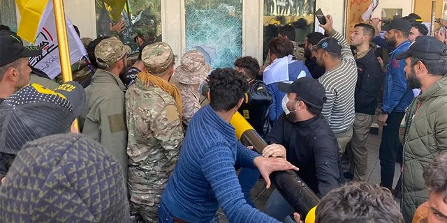 Protesters smash a window inside the U.S. embassy compound in Baghdad on Tuesday. (AP)