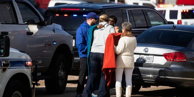 Residents embrace near police and fire cars that surround the scene of a shooting at West Freeway Church of Christ in White Settlement, Texas, Sunday, Dec. 29, 2019.