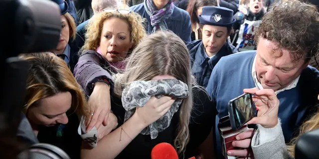 A 19-year-old British woman, center, that was found guilty of making up claims she was raped by up to 12 Israelis arrives at Famagusta District Court for sentencing on Tuesday, Jan. 7, 2020. The woman was found guilty on a charge of public mischief which carries a maximum 1,700 euro fine and one year in jail. The woman insists she was raped and was coerced by investigators to retract her claim. (AP Photo/Petros Karadjias)