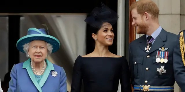 """In this Tuesday, July 10, 2018 file photo Britain's Queen Elizabeth II, and Meghan the Duchess of Sussex and Prince Harry watch a flypast of Royal Air Force aircraft pass over Buckingham Palace in London. As part of a surprise announcement distancing themselves from the British royal family, Prince Harry and his wife Meghan declared they will """"work to become financially independent"""" _ a move that has not been clearly spelled out and could be fraught with obstacles."""