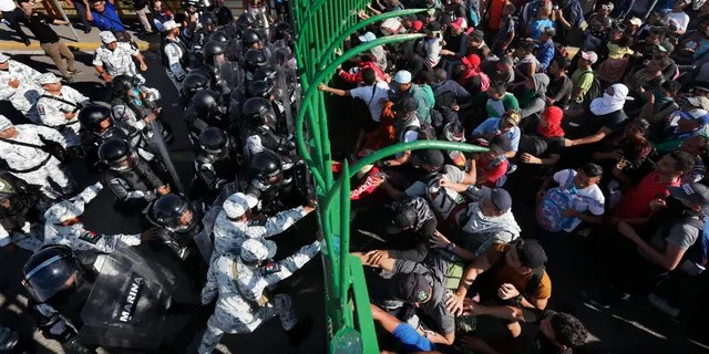 Migrants charge on the Mexican National Guardsmen at the border crossing between Guatemala and Mexico in Tecun Uman, Guatemala, Saturday, Jan. 18, 2020. More than a thousand Central American migrants surged onto the bridge spanning the Suchiate River, that marks the border between both countries, as Mexican security forces attempted to impede their journey north. (AP Photo/Marco Ugarte)