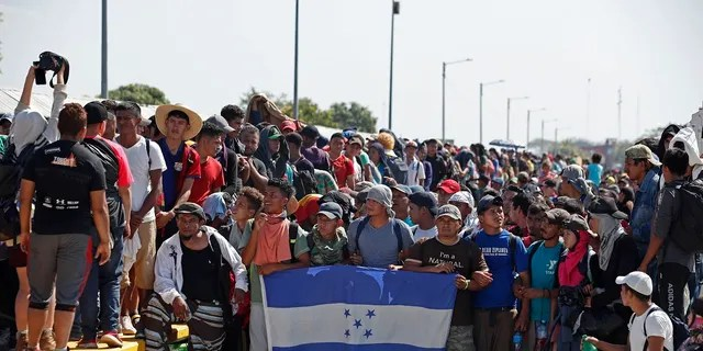 Central American migrants holding Honduras' national flag stand on the legal border crossing bridge over the Suchiate River that connects Tecun Uman, Guatemala with Ciudad Hidalgo in Mexico. (AP Photo/Moises Castillo)