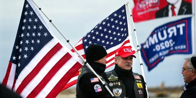 President Donald Trump supporters John Walker, left, and Mike Kufta stand on the Wildwood boardwalk as they wait to attend a campaign rally with Trump, Tuesday, Jan. 28, 2020, in Wildwood, N.J. (AP Photo/Mel Evans)
