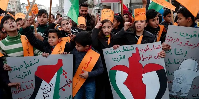 Protesters hold placards as others wave their national flags during a protest against the Mideast plan announced by President Trump, at Jebaliya refugee camp, Gaza Strip, Thursday, Jan. 30, 2020. (AP Photo/Adel Hana)
