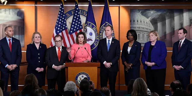 House Speaker Nancy Pelosi of Calif., fourth from left, speaks during a news conference to announce impeachment managers on Capitol Hill in Washington, Wednesday, Jan. 15, 2020. The U.S. House is set to vote Wednesday to send the articles of impeachment against President Donald Trump to the Senate for a landmark trial on whether the charges of abuse of power and obstruction of Congress are grounds for removal. With Pelosi, from left, are Rep. Hakeem Jeffries, D-N.Y., Rep. Sylvia Garcia, D-Texas, House Judiciary Committee Chairman Rep. Jerrold Nadler, D-N.Y., House Intelligence Committee Chairman Rep. Adam Schiff, D-Calif., Rep. Val Demings, D-Fla., Rep. Zoe Lofgren, D-Calif., and Rep. Jason Crow, D-Colo. (AP Photo/Susan Walsh)