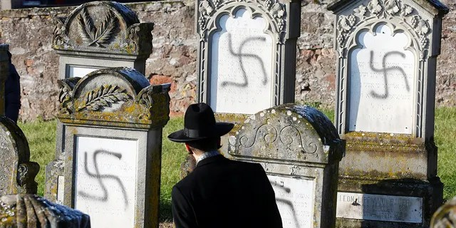 Chief Rabbi Harold Abraham Weill looks at graves desecrated with swastikas at the Jewish cemetery in Westhoffen, near Strasbourg, France, December 4, 2019. (REUTERS/Arnd Wiegmann)