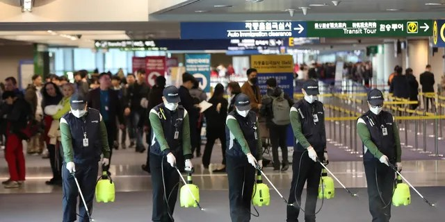 Workers spray antiseptic solution on the arrival lobby amid rising public concerns over the possible spread of a new coronavirus at Incheon International Airport in Incheon, South Korea, Tuesday, Jan. 21, 2020.