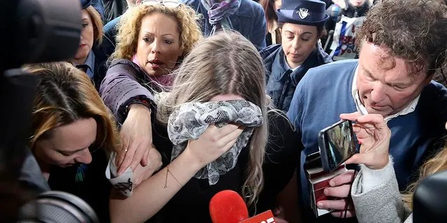 A 19-year-old British woman, center, who was found guilty of making up claims she was raped by up to 12 Israelis arrives at Famagusta District Court for sentencing on Tuesday, Jan. 7, 2020. She insisted she was raped and was coerced by investigators to retract her claim. (AP Photo/Petros Karadjias)