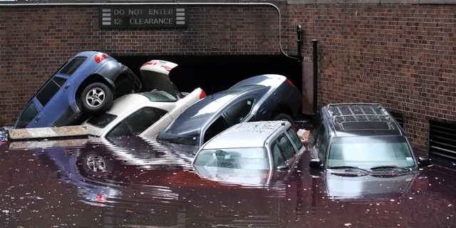 Cars piled on top of each other at the entrance to a garage on South Willliam Street in Lower Manhattan October 31, 2012 in New York as the city begins to clean up after Hurricane Sandy. AFP PHOTO/Stan HONDA (Photo credit should read STAN HONDA/AFP via Getty Images)