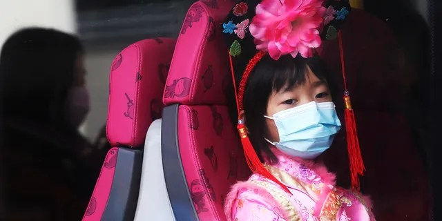 A girl wears a mask inside a bus in Hong Kong, Saturday, Jan. 25, 2020.