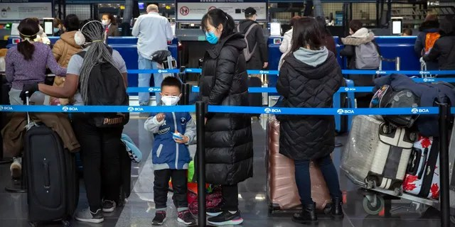 Travelers wearing face masks line up to check in for an American Airlines flight to Los Angeles at Beijing Capital International Airport in Beijing on Jan. 30. (AP Photo/Mark Schiefelbein)