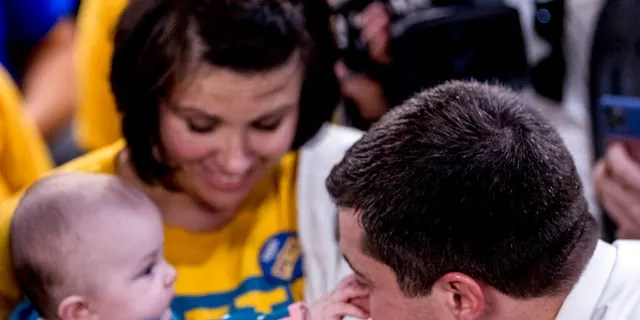 Tara Hansen of West Des Moines, Iowa, holds her granddaughter Emmy who grabs the nose of Democratic presidential candidate former South Bend, Ind., Mayor Pete Buttigieg as he visits supporters at a campaign office the day of the Iowa Caucus, Monday, Feb. 3, 2020, in West Des Moines, Iowa. (AP Photo/Andrew Harnik)