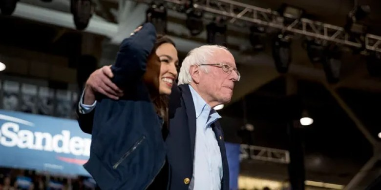 Democratic presidential candidate Sen. Bernie Sanders, I-Vt., accompanied by Rep. Alexandria Oa casio-Cortez, D-N.Y., left, takes the stage at campaign stop at the Whittemore Center Arena at the University of New Hampshire, Monday, Feb. 10, 2020, in Durham, N.H. (AP Photo/Andrew Harnik)