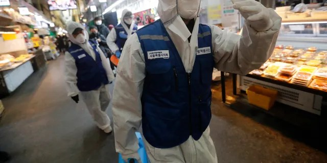 """Workers wearing protective gears arrive to spray disinfectant as a precaution against the coronavirus at a market in Seoul, South Korea, Monday, Feb. 24, 2020. South Korean President Moon Jae-in said his government had increased its anti-virus alert level by one notch to """"Red,"""" the highest level. It allows for the temporary closure of schools and reduced operation of public transportation and flights to and from South Korea. (AP Photo/Ahn Young-joon)"""