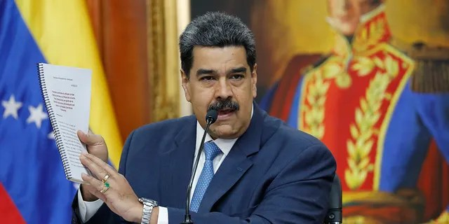 Venezuelan President Nicolas Maduro holds up a copy of his country's case taken to the International Criminal Court regarding U.S. sanctions during a press conference at Miraflores presidential palace in Caracas, Venezuela, on Friday.