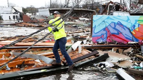 A man makes his way through debris following a deadly tornado Tuesday, March 3, 2020, in Nashville, Tenn.