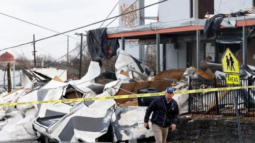 A man walks past storm debris following a deadly tornado, Tuesday, March 3, 2020, in Nashville, Tenn.