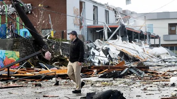 A man walks past storm debris following a deadly tornado Tuesday, March 3, 2020, in Nashville, Tenn.