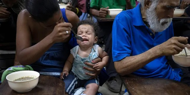 Zoraida Silva, 26, feeds her six month baby Jhon Angel, at a soup kitchen in The Cemetery slum, in Caracas, Venezuela. Silva said that she can not afford to have 3 meals a day, and she has been eating at the soup kitchen for two years ago. According to a survey recently published by the U.N. World Food Program, one of every three Venezuelans cope with food insecurity, unable to get enough food to meet their basic dietary needs.