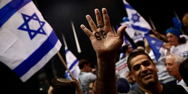 """Supporter of Israeli Prime Minister Benjamin Netanyahu displays his hand with BB written on it for Netanyahu's nickname """"Bibi"""" as they celebrate after first exit poll results for Israeli elections in Tel Aviv, Israel, Monday. (AP Photo/Oded Balilty)"""