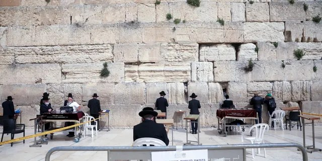 Ultra Orthodox Jews pray at the Western Wall in Jerusalem, Sunday, March 15, 2020. Israel imposed sweeping travel and quarantine measures more than a week ago but has seen its number of confirmed coronavirus cases double in recent days, to around 200. On Saturday, the government said restaurants, malls, cinemas, gyms and daycare centers would close. (AP Photo/Mahmoud Illean)