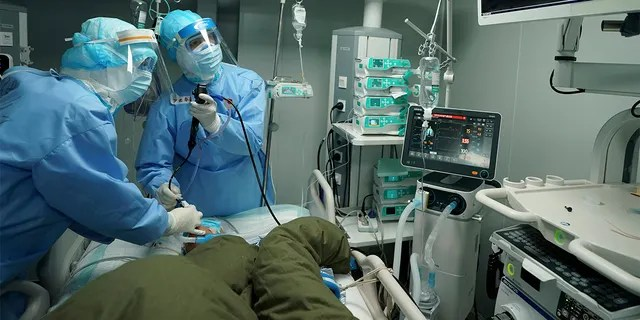 In this March 17, 2020 photo released by China's Xinhua News Agency, medical workers use a bronchoscope to treat a coronavirus patient at the Huoshenshan field hospital in Wuhan in central China's Hubei Province. Last month, Wuhan was overwhelmed with thousands of new cases of coronavirus each day.