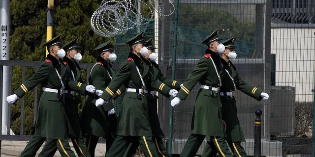 Chinese paramilitary wearing masks march by during their duty in an embassy district in Beijing on Monday, March 16, 2020. With more imported cases of the new coronavirus, starting Monday, travelers arriving in Beijing from overseas will be quarantined for 14 days in designated facilities at their own expense. For most people, the new coronavirus causes only mild or moderate symptoms. For some it can cause more severe illness. (AP Photo/Ng Han Guan)