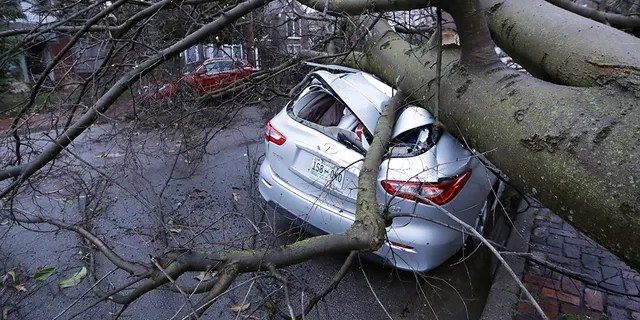 A car crushed by a tree sits on a street after a tornado touched down Tuesday, March 3, 2020, in Nashville, Tenn.