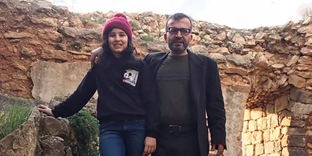Ismail Mousa and his daughter Anisa of Selbyville, Del., pose for a photograph on March 12 while sightseeing near the Palestinian village of Qaryout in the West Bank. (Reem Mousa via AP)