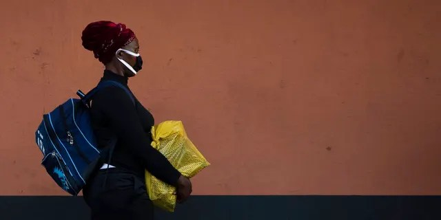 A woman, wearing a protective mask as a precaution against the spread of the new coronavirus, carries her groceries while walking the street in Johannesburg, South Africa.