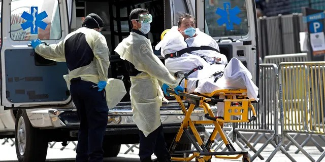 A patient is wheeled out of Elmhurst Hospital Center to a waiting ambulance, Tuesday, April 7, 2020, in the Queens borough of New York, during the current coronavirus outbreak. COVID-19, the disease caused by the novel coronavirus, is now the No. 1 cause of death in the U.S. -- killing more people on average per day than cancer or heart disease. (AP Photo/Kathy Willens)
