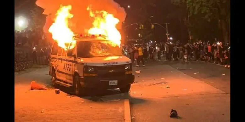 A police van goes up in flames in New York City.