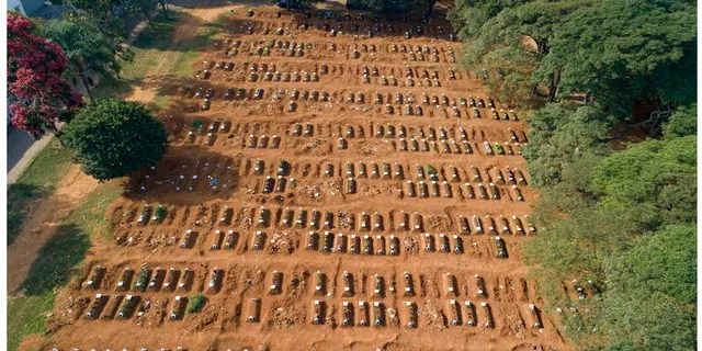 This combo shows freshly dug graves, top, on April 1, 2020 at the Vila Formosa cemetery in Sao Paulo, Brazil, compared to one month later on April 30 with the graves filled in. Sao Paulo authorities dug hundreds of new graves in anticipation of an increase in the city's death rate amid the presence of the new coronavirus pandemic. (AP Photo/Andre Penner)