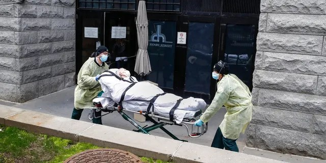 In this Friday, April 17, 2020 file photo, a patient is wheeled out of the Cobble Hill Health Center by emergency medical workers in the Brooklyn borough of New York.