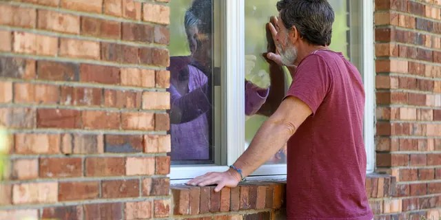 Jack Campise talks with his mother, Beverly Kearns, through her apartment window at the Kimberly Hall North nursing home in Windsor, Conn.