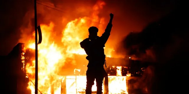In this May 29, 2020, photo, a check-cashing business burns during protests in Minneapolis. Protests continued following the death of George Floyd, who died after being restrained by Minneapolis police officers on Memorial Day.