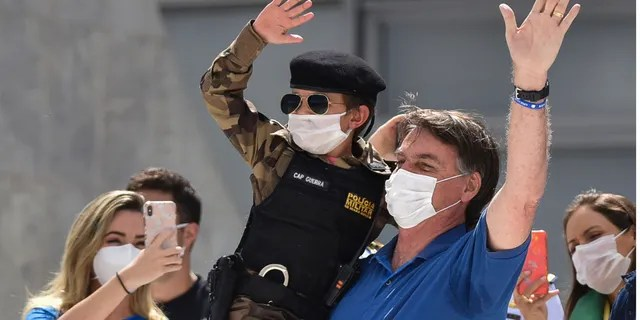 Brazil's President Jair Bolsonaro, wearing a mask against the spread of the new coronavirus, carries a child dressed in military policeman's uniform during a protest against the Supreme Court and Brazil's National Congress, to back his open-the-economy drive amid the pandemic, in Brasilia, Brazil, Sunday, May 17, 2020. Bolsonaro greeted hundreds of supporters who gathered at the presidential residence to back his open-the-economy drive even as the COVID-19 pandemic sweeps across the country. (AP Photo/Andre Borges)