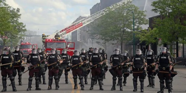 Minnesota state troopers provide protection as firefighters battle a fire, May 29, after another night of protests, fires and looting over the arrest of George Floyd. (AP Photo/Jim Mone)