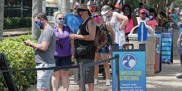 Гости ждут своей очереди, чтобы измерить их температуру, прежде чем войти в SeaWorld, поскольку он вновь откроется с новыми мерами безопасности, в четверг, 11 июня 2020 года, в Орландо, штат Флорида. Парк был закрыт с середины марта, чтобы остановить распространение коронавируса. , (AP Photo / John Raoux)