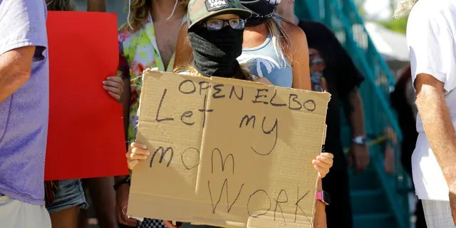 """Bartender Kat DeLaTorre stands with her son Nico, 12, during a """"Right to Work"""" rally outside of the Elbo Room bar, which remains closed, during the new coronavirus pandemic, June 16, in Fort Lauderdale, Fla."""