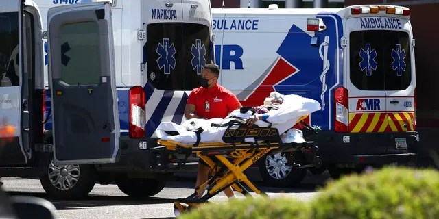 A person is brought to a medical transport vehicle from Banner Desert Medical Center as several transports and ambulances are shown parked outside the emergency room entrance, June 16, in Mesa, Ariz.