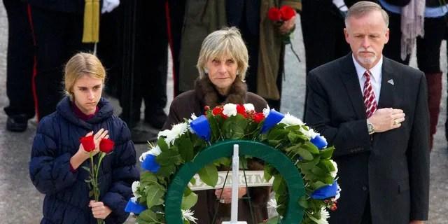 FICHIER - Dans ce Nov. 22, 2013 fichier photo, Un inconnu jeune fille, à gauche, tient une rose au cours d'une cérémonie de dépôt de gerbe avec l'ancien Ambassadeur d'Irlande Jean Kennedy Smith, au centre, et Patrick Hallinan, directeur exécutif de l'Armée Nationale Cimetières Militaires, sur la tombe de John F. Kennedy, au Cimetière National d'Arlington à Arlington, en Virginie. Jean Kennedy Smith, la plus jeune sœur et le dernier survivant de la fratrie du Président John F. Kennedy, est décédé à 92 ans, sa fille a confirmé Au New York Times, mercredi, le 17 juin 2020. (AP Photo/Jacquelyn Martin)