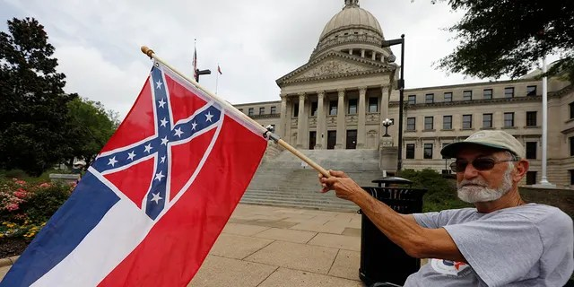 Star's Larry Eubanks waves the current Mississippi state flag as he sat in front of the Capitol Building on Saturday June 27, 2020 in Jackson, Mississippi (Associated Press)
