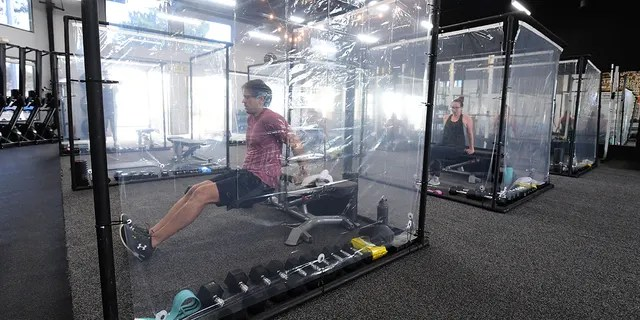 People exercise at Inspire South Bay Fitness behind plastic sheets in their workout pods while observing social distancing on June 15.