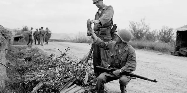 First Lt. John R. Grimes (left), Milledgeville, Georgia, and Staff Sgt.  George H. Trout, Richland, Pennsylvania, examines the mortar shells that the North Koreans left in a highway ditch quickly fleeing the city of Waegwan in Korea on September 27, 1950. (AP Photo / Gene Herrick)