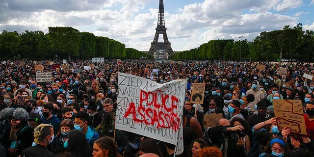 Hundreds of demonstrators gathering on the Champs de Mars as the Eiffel Tower is seen in the background during a demonstration in Paris earlier this month. (AP Photo/Francois Mori, File)