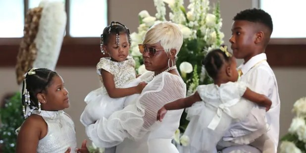 Tomika Miller, the wife of Rayshard Brooks, is holding her 2-year-old daughter, Memory, as she pauses with her children during the family procession at her funeral at Ebenezer Baptist Church in Atlanta on Tuesday.  (Curtis Compton / Atlanta Journal-Constitution via AP, Pool)