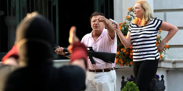 Armed homeowners standing in front of their house along Portland Place confront protesters on June 28, in the Central West End in St. Louis. (Laurie Skrivan/St. Louis Post-Dispatch/Tribune News Service via Getty Images)