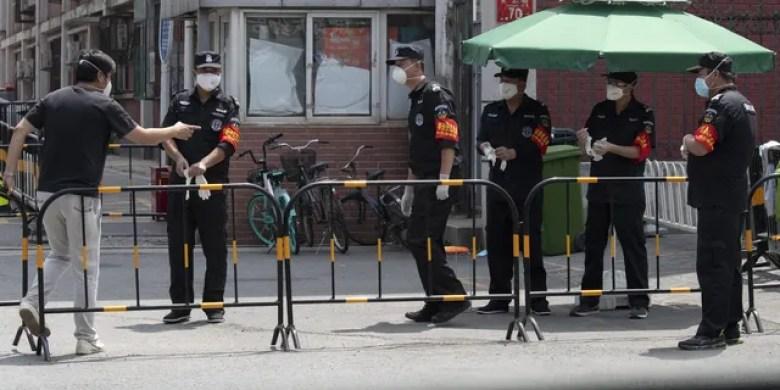 Security guards prepare for duty near a neighborhood under lockdown in Beijing on Tuesday. (AP)